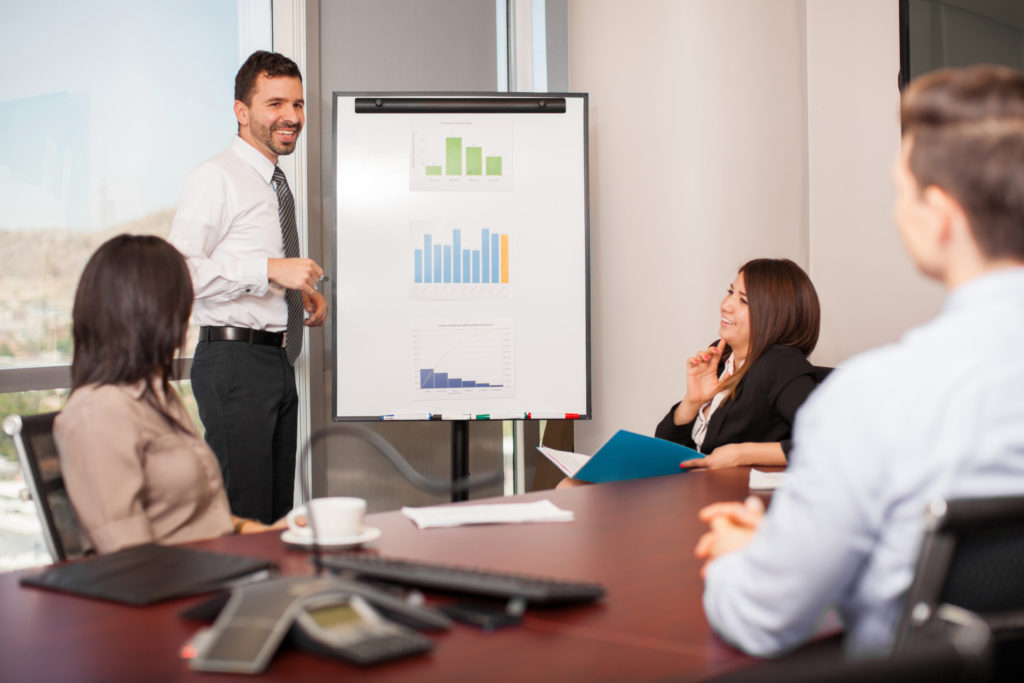 Attractive young man giving a sales pitch to a group of clients in a meeting room