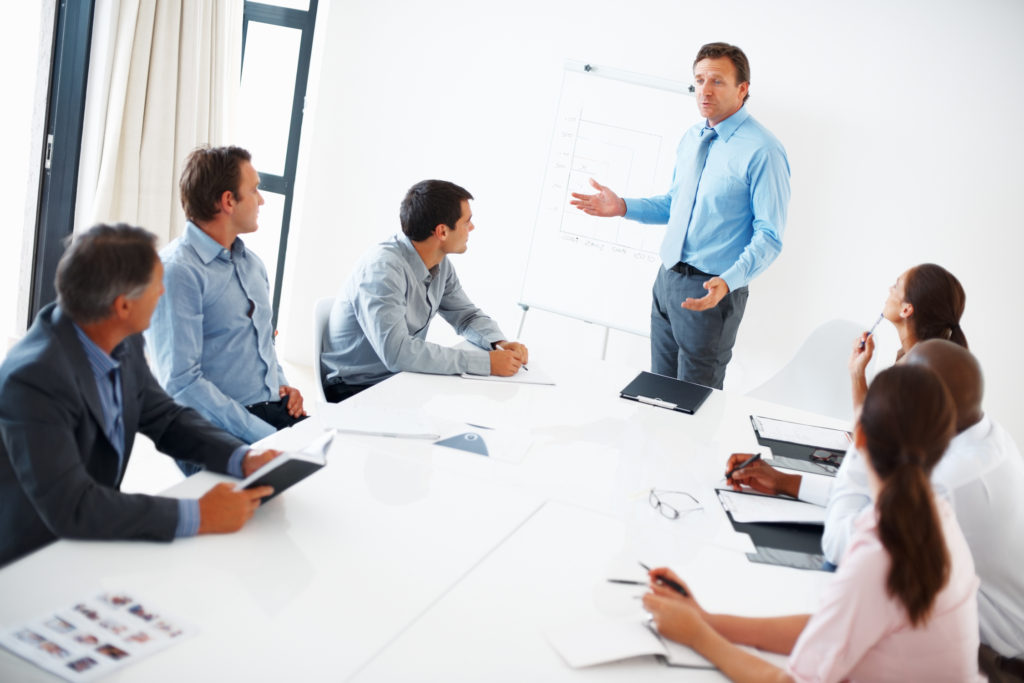 Mature team leader giving presentation to his team