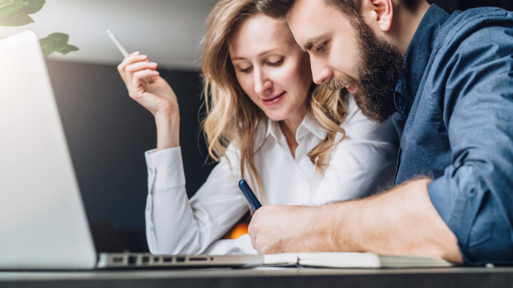 Businessman and businesswoman are sitting at table in front of laptop, discussing business concept. Man is writing pen in notebook, woman is holding white pencil. Teamwork. Online marketing, education